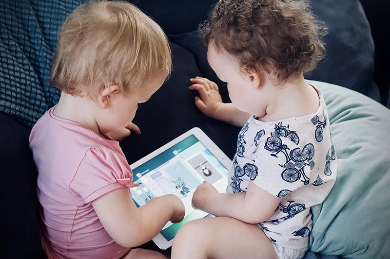 Deux bambins passent du temps devant l'écran d'une tablette électronique.